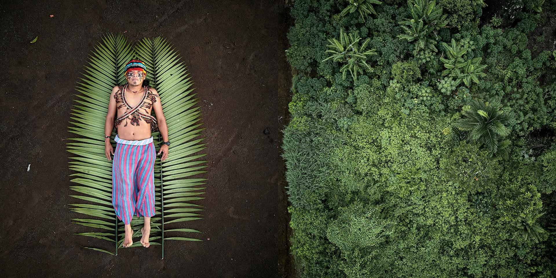 Una persona con il costume tradizionale sdraiata a terra in una foresta