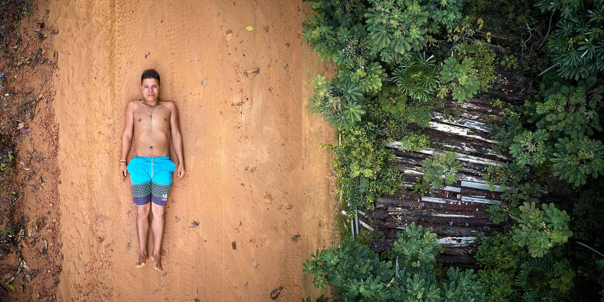 Persona sdraiata a terra accanto ad una foresta