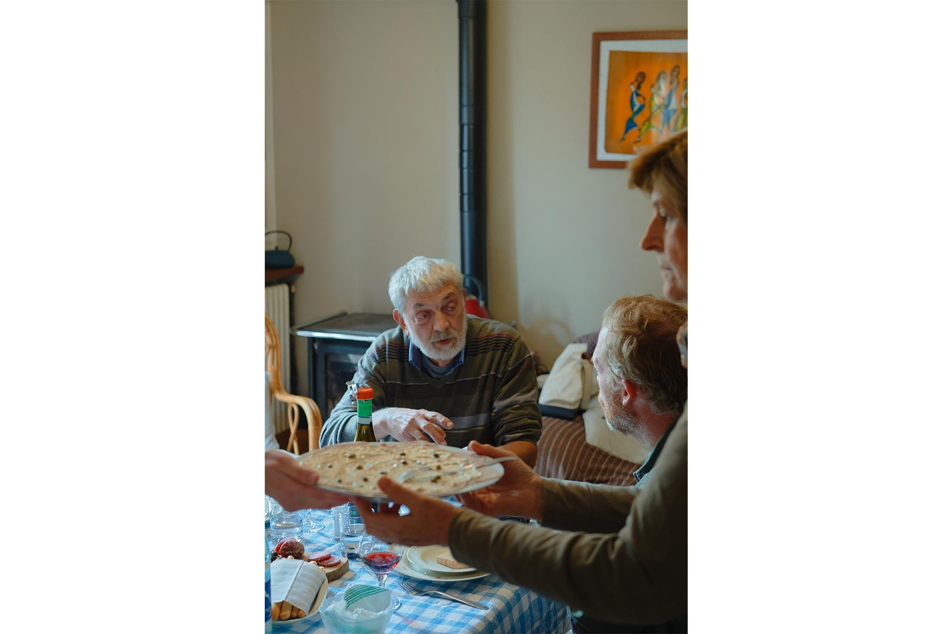 un anziano cacciatore di tartufi a tavola con la sua famiglia